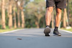 Young fitness man legs walking in the park outdoor. male runner running on the road outside. Asian athlete jogging and exercise on. Footpath in sunlight morning royalty free stock photography