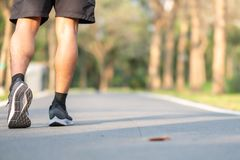 Young fitness man legs walking in the park outdoor. male runner running on the road outside. Asian athlete jogging and exercise on. Footpath in sunlight morning royalty free stock photos