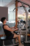 Asian chinese man in gym ,Fitness sport man lifts in the gym. Young fitness man lifts in the simulator in the gym , Weight Training At Gym Royalty Free Stock Image