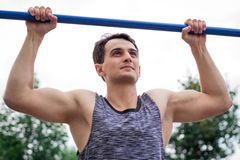 Young fitness man lifts up on horizontal bar during workout Royalty Free Stock Photo