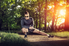 Young fitness man runner stretching legs before run. Young  man runner stretching legs before run Stock Image