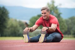 Young Fitness Man Runner Stretching Legs Before Run. Portrait of Fit and Sporty Young Man Doing Stretching in the Park Royalty Free Stock Images