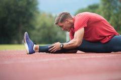 Young Fitness Man Runner Stretching Legs Before Run. Young Athlete Man Relax and Strech Ready for Run at Athletics Race Track on Stadium Stock Image