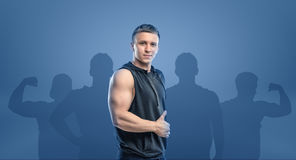 Young fitness man standing sideways and showing thumb up. Inwardness. Self-perfection. Self improvement. Fitness and sport stock image