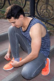 Young fitness man ties up shoelaces on his sport footwear Stock Photo