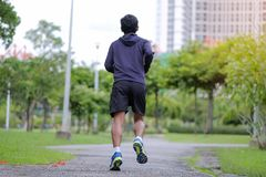 Young fitness man walking in the park outdoor, runner running on the road outside, asian athlete jogging and exercise on footpath. In sunlight morning. Sport royalty free stock photography