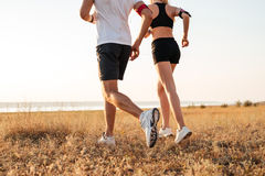 Young fitness man and woman doing jogging sport outdoors. Cropped image of a young fitness men and women doing jogging sport outdoors royalty free stock photo