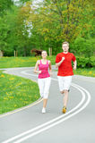 Young man and woman jogging outdoors. Young fitness men and women doing jogging sport outdoors Royalty Free Stock Photos