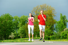 Young man and woman jogging outdoors. Young fitness men and women doing jogging sport outdoors Royalty Free Stock Photo