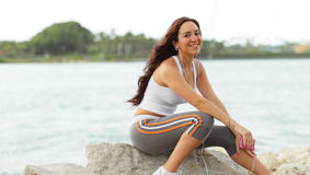 Young fitness model sitting on the rocks Royalty Free Stock Image