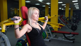 Young fitness model works out on training apparatus inside in fitness center. Attractive young fitness model works out on training apparatus inside in fitness stock footage