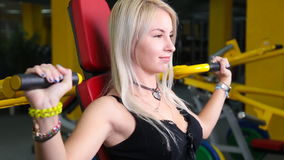Young fitness model works out on training apparatus inside in fitness center. Attractive young fitness model works out on training apparatus inside in fitness stock video footage