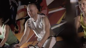 Young fitness people working out on exercise bicycles against colorful background. Slow motion stock footage