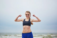 Young fitness running woman doing exercise on beach. Healthy fitness runner girl wearing sunglasses showing her biceps. Young European woman on beach cardio Stock Images