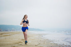 Young fitness running woman jogging on beach Royalty Free Stock Photos