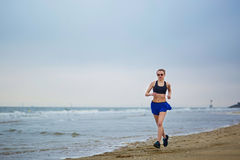 Young fitness running woman jogging on beach. Young fitness running woman jogging fast on beach near ocean or sea on a foggy misty morning. Fitness and healthy Royalty Free Stock Photo