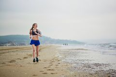Young fitness running woman jogging on beach. Young fitness running woman jogging fast on beach near ocean or sea on a foggy misty morning. Fitness and healthy Royalty Free Stock Images