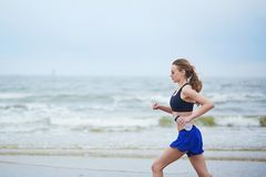 Young fitness running woman jogging on beach. Young fitness running woman jogging fast on beach near ocean or sea on a foggy misty morning. Fitness and healthy Stock Images