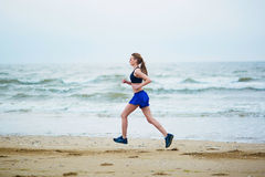 Young fitness running woman jogging on beach Stock Photos