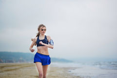 Young fitness running woman jogging on beach Stock Photography