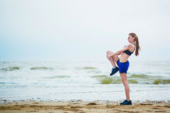 Young fitness running woman stretching on beach. Fitness woman on beach doing stretching exercise after a workout. Jogger stretching muscles after run near sea Stock Photography