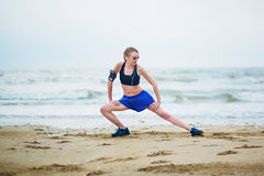 Young fitness running woman stretching on beach. Fitness woman on beach doing stretching exercise after a workout. Jogger stretching muscles after run near sea Royalty Free Stock Photo