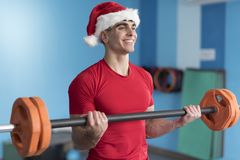 Young fitness Santa Claus training in gym lifting weights with b. Ar while smiling Stock Image