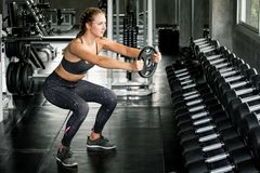 Free Young Fitness Sport Girl Doing Exercise Squat With Weight Barbell Plate In Gym.woman In Sportswear Workout Strengthen Pumping Up Stock Photo - 150151840