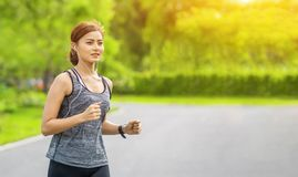 Young fitness sport woman running on the road in the morning, Young fitness sportswoman runner running on tropical park trail. Peo. Ple and sport concept stock photography