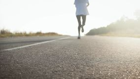 Young fitness sport woman running on road at sunset. Athlete runner feet running on road, slow motion. Young fitness sport woman running on road at sunset stock video