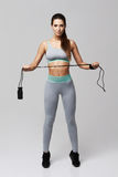 Young fitness sportive girl posing looking at camera holding jumping rope over white background. Copy space Royalty Free Stock Photography