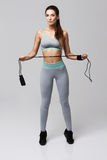 Young fitness sportive girl posing looking at camera holding jumping rope over white background. Copy space Stock Photos