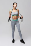 Young fitness sportive girl posing looking at camera holding jumping rope over white background. Copy space Stock Image