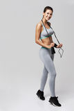Young fitness sportive girl posing smiling holding jumping rope over white background. Copy space Stock Photos