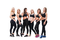 Young fitness trainers in black tops and leggings. Young and pretty fitness trainers in black tops and leggings posing in group in studio Stock Image