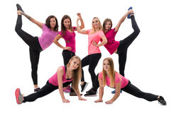 Young fitness trainers in bright tops and leggings. Young and pretty fitness trainers in bright tops and leggings posing in group in studio Royalty Free Stock Photos