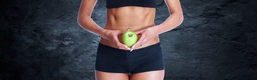 Young fitness woman abdomen with apple. Royalty Free Stock Photography