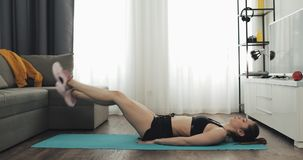 Young fitness woman in athletic workout clothes doing exercise from mat while using a stopwatch on her smartphone. She. Is training at home. Healthy and sport stock footage