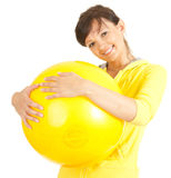Young fitness woman with big yellow ball, Royalty Free Stock Photography