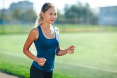 Young fitness woman in a blue shirt and leggings running on a stadium track. Athlete girl doing exercises on the training at stadi. Um. Healthy active lifestyle royalty free stock photography