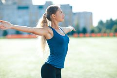 Young fitness woman in a blue shirt and leggings smile spread her hands to the sky for success in waiting the sun shines in her fa. Ce, in stadium on the Royalty Free Stock Images