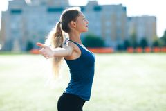 Young fitness woman in a blue shirt and leggings smile spread her hands to the sky for success in waiting the sun shines in her fa. Ce, in stadium on the Stock Image