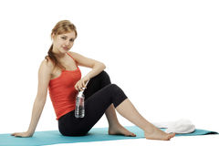 Young fitness woman with a bottle of water sitting Royalty Free Stock Images