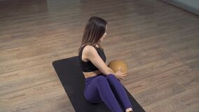 Young fitness woman doing abdominal muscles exercises with a ball at home or in the studio.