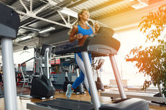 Young fitness woman doing cardio exercises at the gym running on a treadmill. Stock Photography