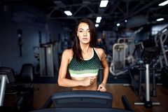 Young fitness woman doing cardio exercises at the gym running on a treadmill. Female runner training at the health club Royalty Free Stock Images
