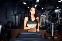Young fitness woman doing cardio exercises at the gym running on a treadmill. Female runner training at the health club Royalty Free Stock Photos