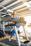 Young fitness woman doing cardio exercises at the gym running on a treadmill. Female runner training at the health club Stock Image