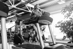 Young fitness woman doing cardio exercises at the gym running on a treadmill. Female runner training at the health club Stock Photo