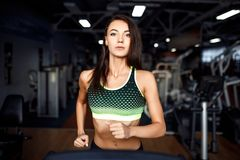 Young fitness woman doing cardio exercises at the gym running on a treadmill. Female runner training at the health club Stock Photos